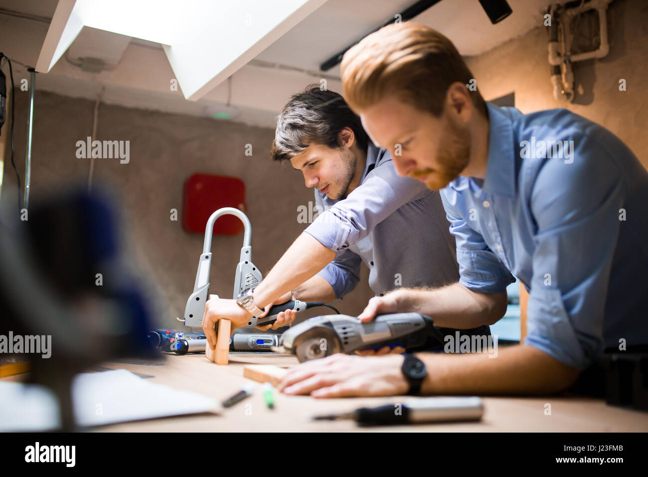 Two designers working on a project in workshop with joint effort - Stock Image