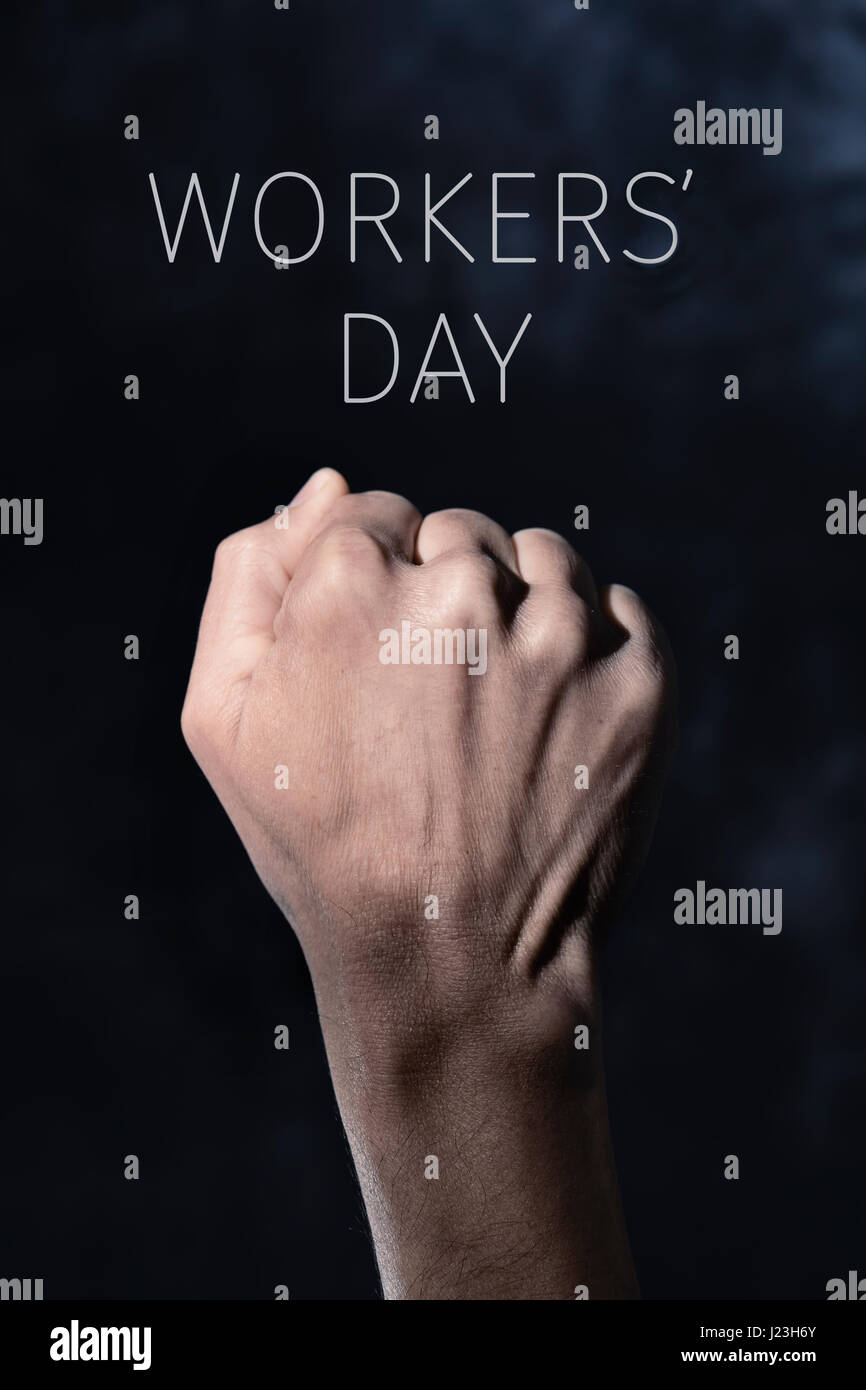 closeup of the raised fist of a young man against a gradient dark gray background and the text workers day - Stock Image