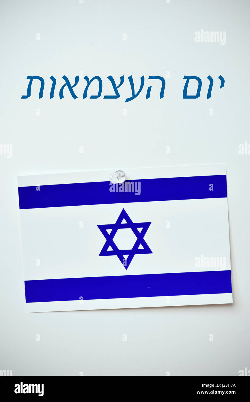 the text day of israel written in hebrew and an israeli flag pinned with a push-pin to an off-white background - Stock Image