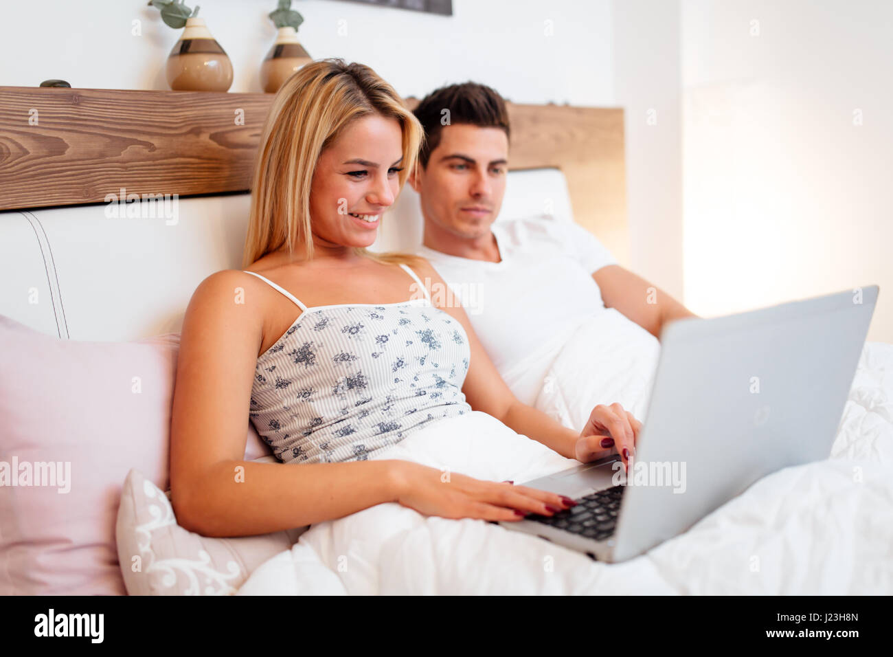 Couple in bed reading news on notebook after waking up - Stock Image