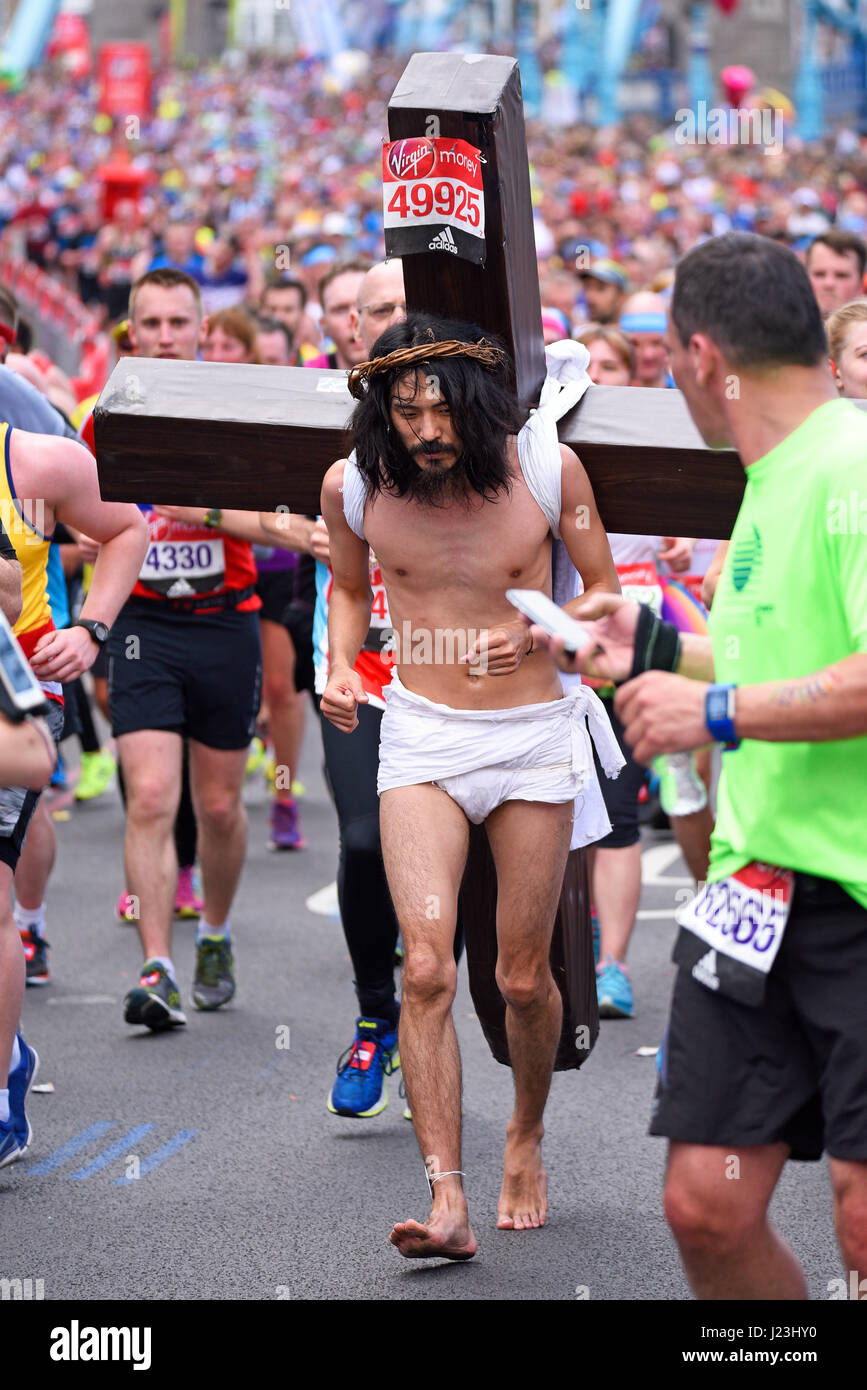 Makoto Takeuchi as Christ at the 2017 Virgin London Marathon after crossing Tower Bridge and alongside the Tower - Stock Image