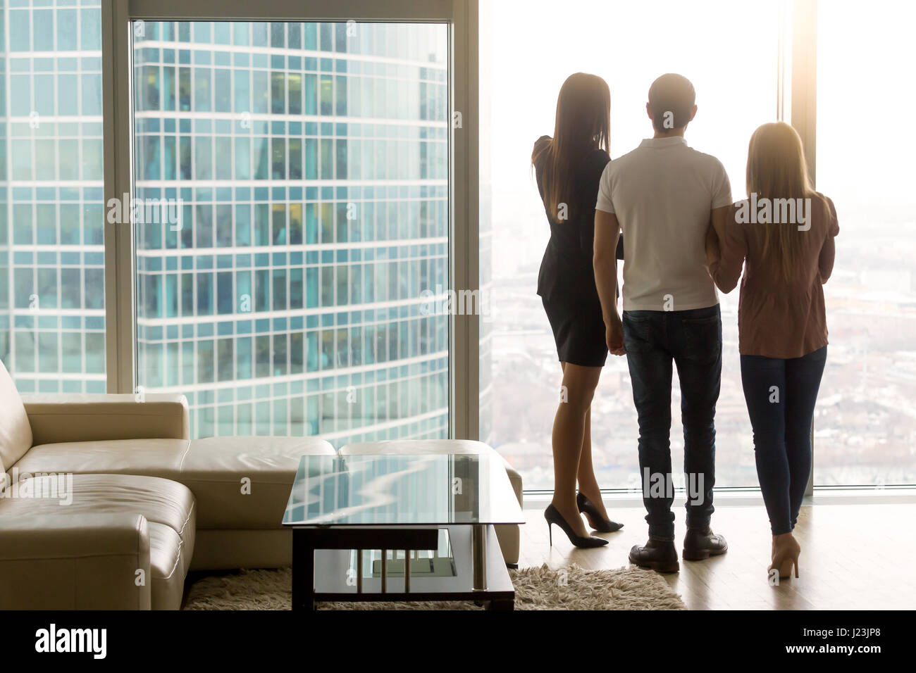 Man and two women looking out the window, rear view - Stock Image