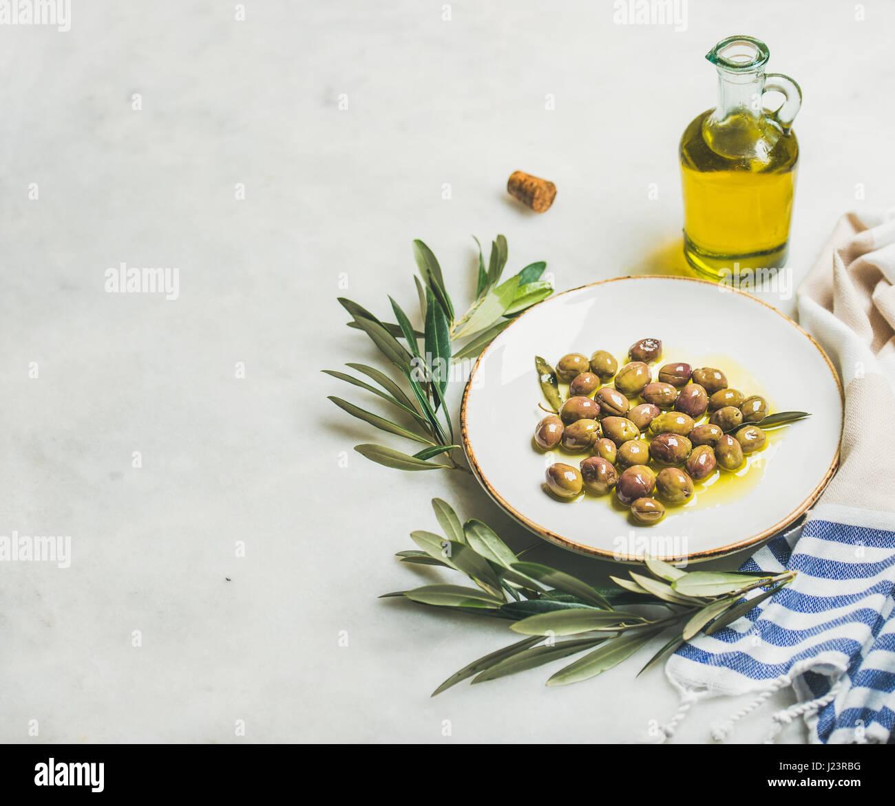 Pickled green Mediterranean olives, olive tree branch and virgin oil - Stock Image