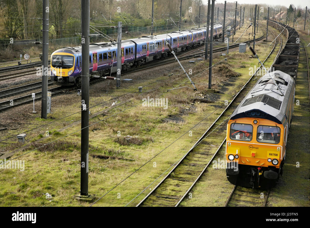 TransPennine Express train approaching York station, UK with GBRF class 66 loco 66708 waiting at Holgate sidings. - Stock Image