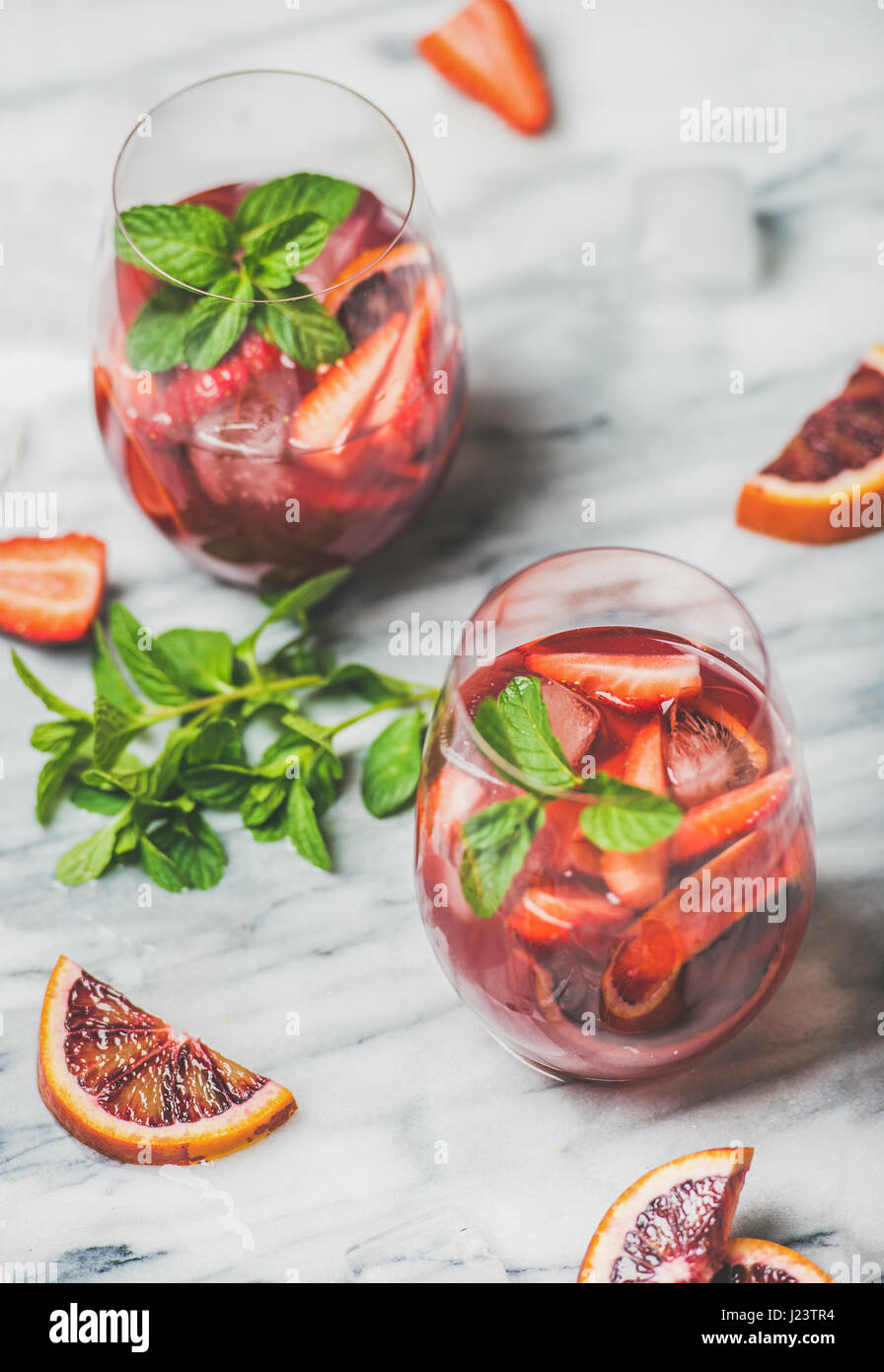 Fruit refreshing Sangria cocktails in glasses with ice and mint - Stock Image
