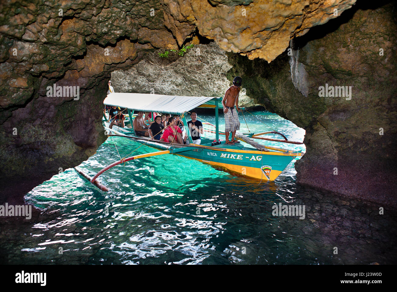 Pontoon tour boat full of tourists enter Baras Cave while island hopping in the Guimaras Islands, Philippines. - Stock Image