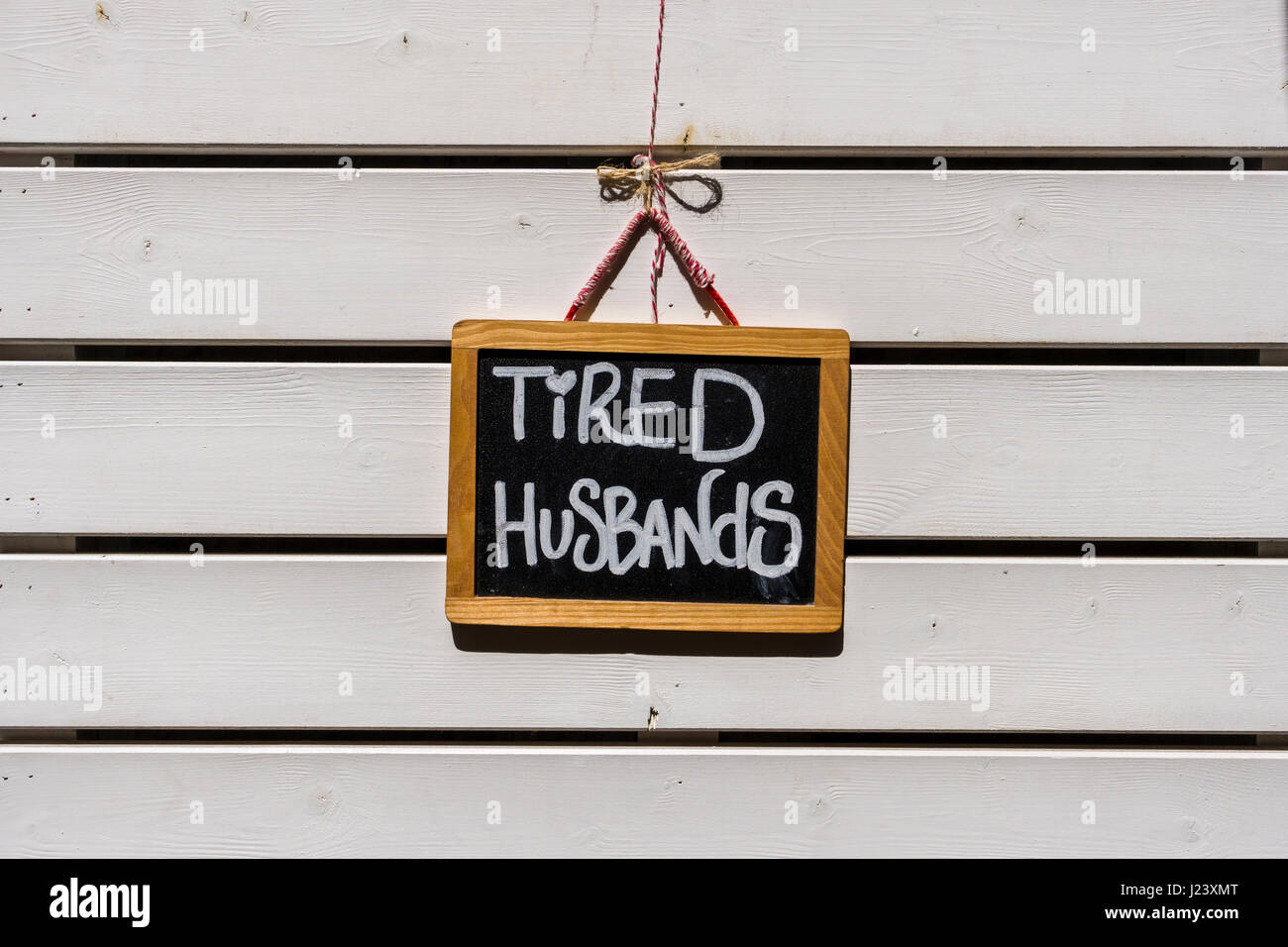 The sign Tired Husbands is inviting to sit on a chair - Stock Image