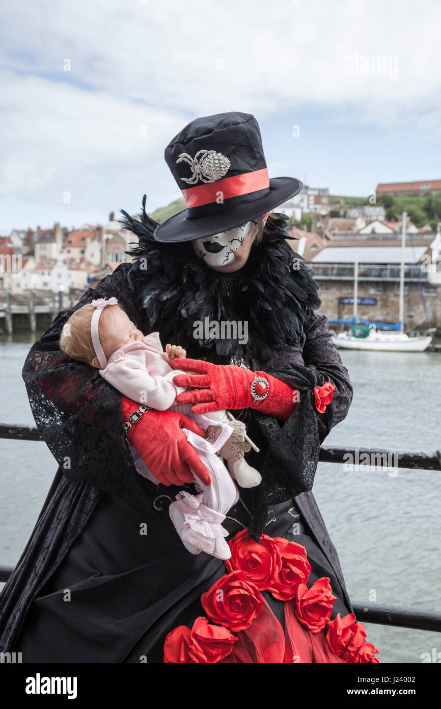 A female Goth stood cradling a lifelike baby doll at Whitby seafront at the biannual Goth Weekend celebrations - Stock Image
