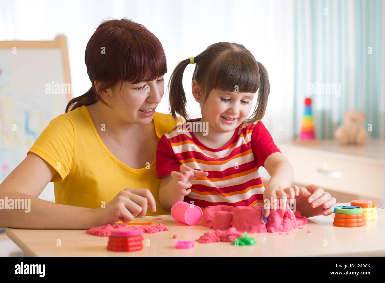 A cute little little girl and her mom playing with kinetic sand at home - Stock Image