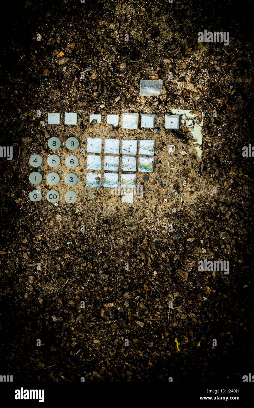 An electronic keyboard buried in dirt, signifying a post apocalytic world - Stock Image