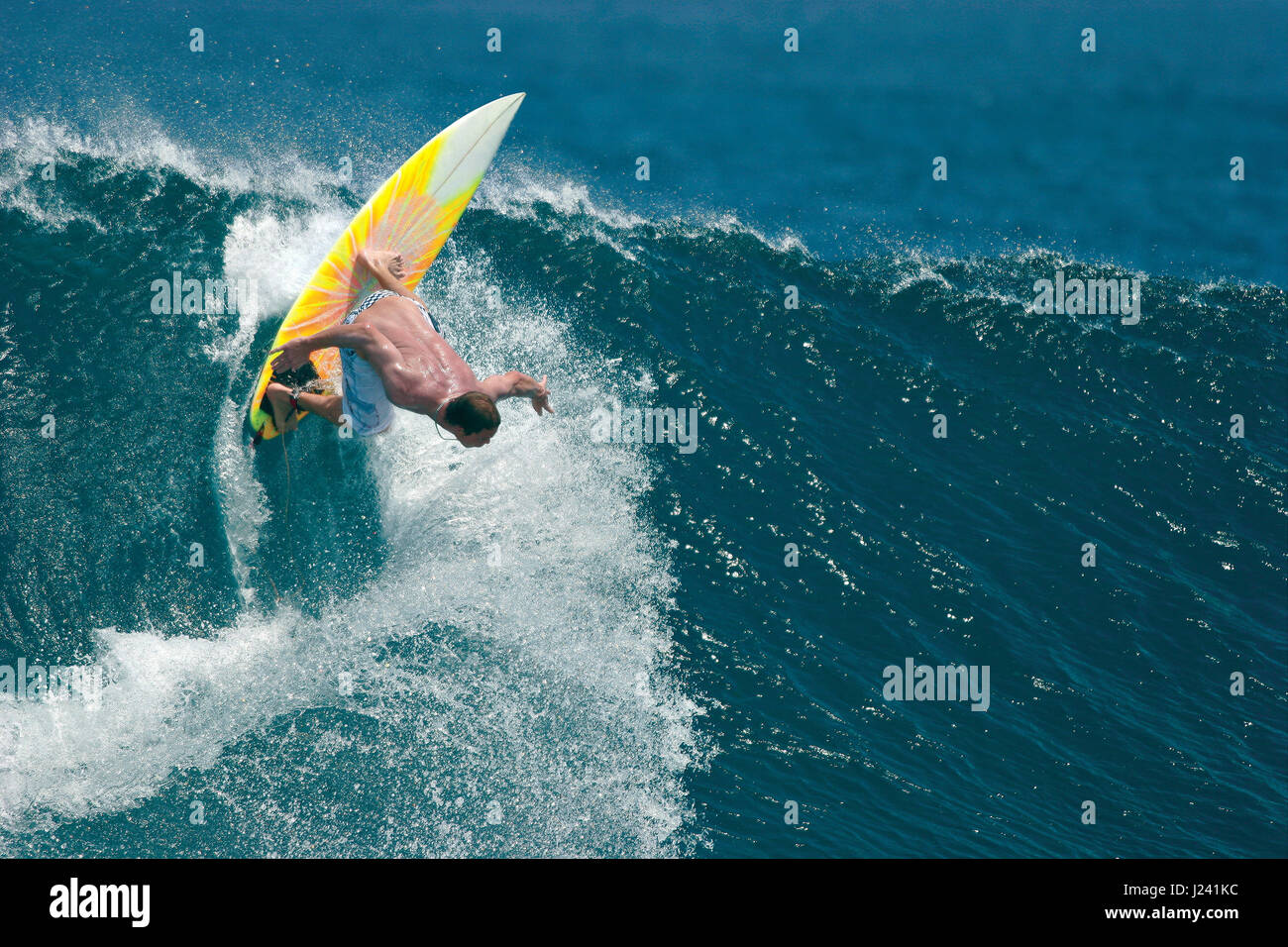 A surfer executes a radical backhand move on a beautiful blue ocean wave. - Stock Image