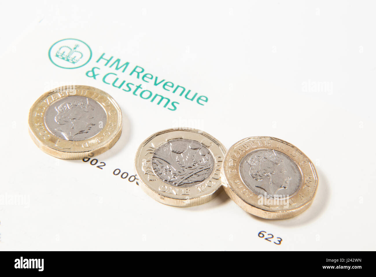 New £1 coins and £2 pound coins on a HM Revenue & Customs letter - Stock Image