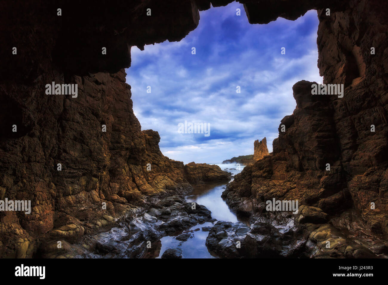 Rocky cave towards open sea at sunset near Bombo beach and Cathedral rocks of Pacific coast in Australia. - Stock Image