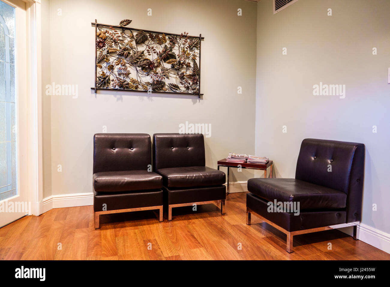 Miami Beach Florida waiting room doctor's office austere black leather chairs wall decor hardwood flooring plain - Stock Image