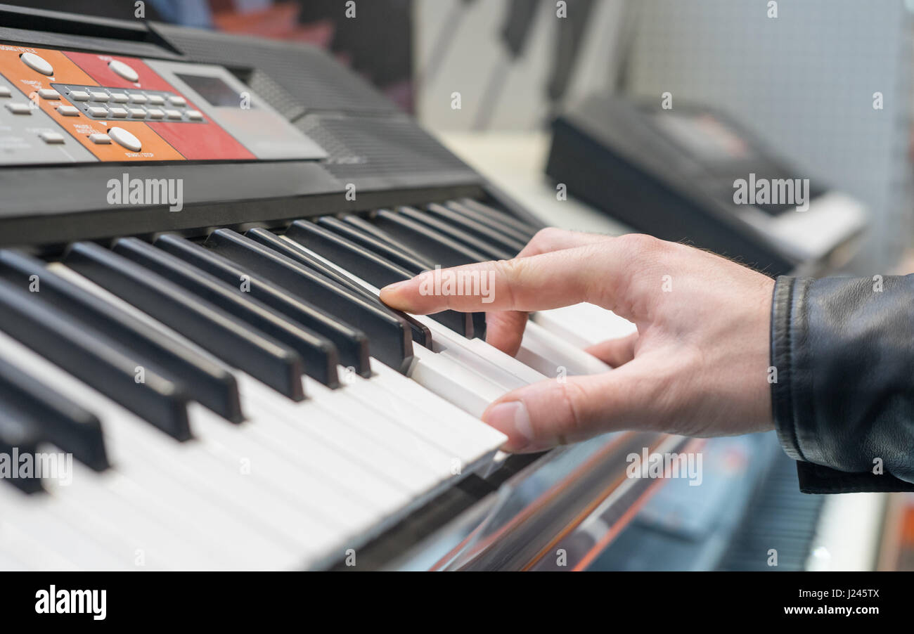 piano keyboard synthesizer with hand - Stock Image