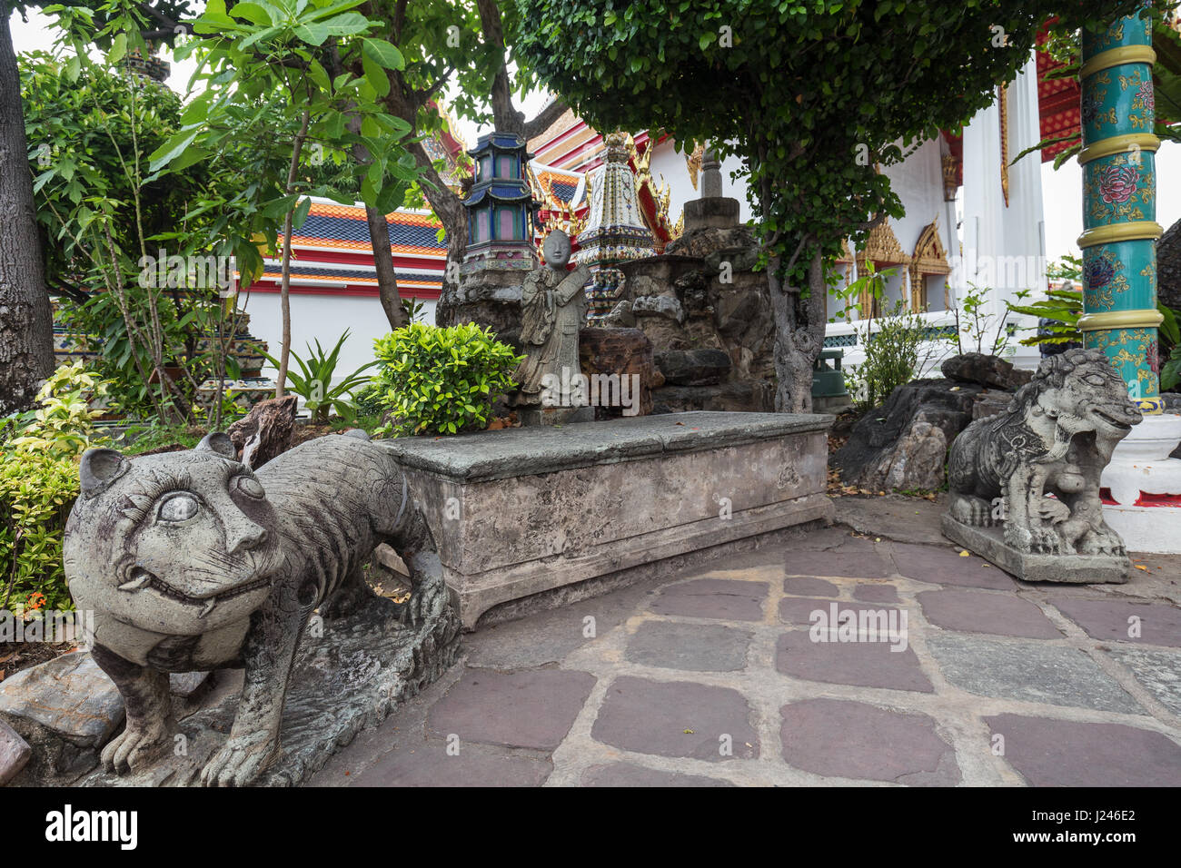 Statues and trees at the Wat Pho (Po) temple complex in Bangkok, Thailand. - Stock Image
