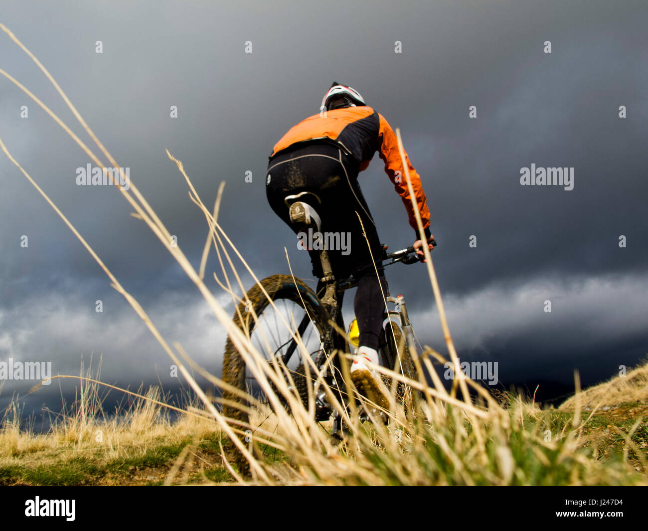Mountain Bike rider under a stormy sky - Stock Image