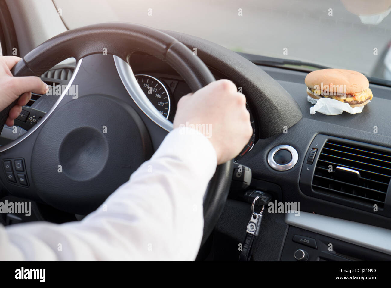 Man eating junk food and driving seated in his car - Stock Image