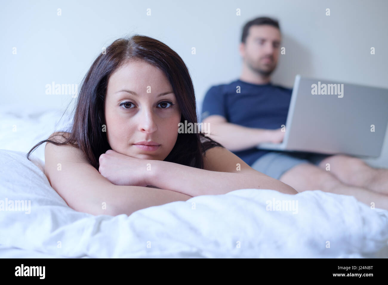 Bored couple lying in the bed , man is neglecting his girlfriend internet - Stock Image