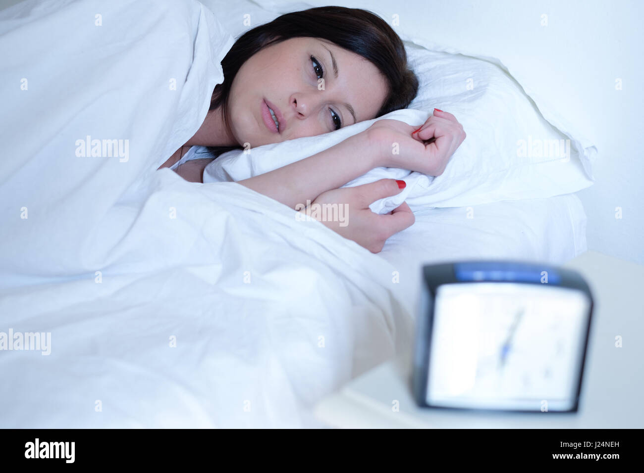 Woman waking up early in the morning , main focus on the woman face - Stock Image