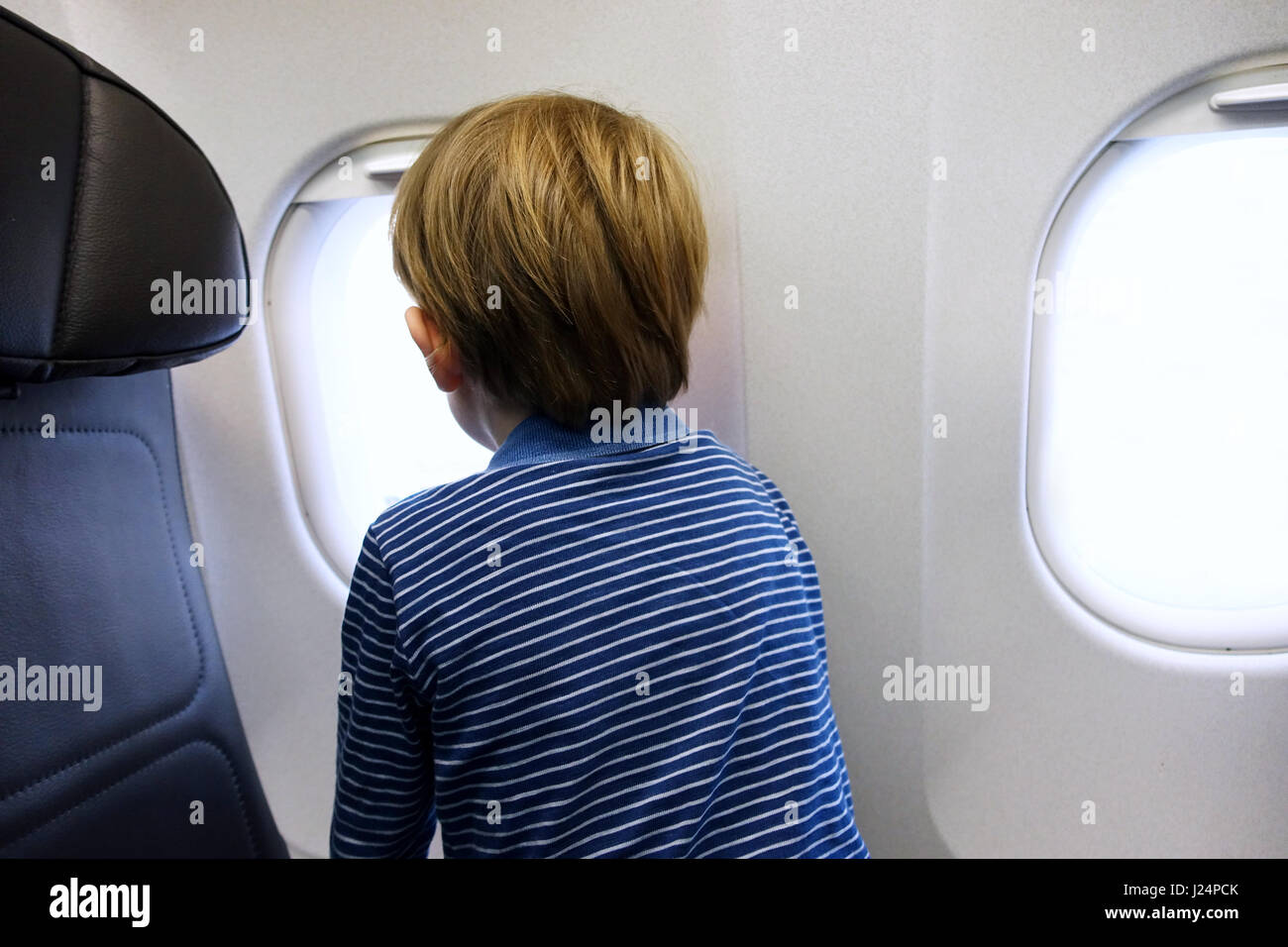 Little boy looking out of aeroplane window - Stock Image