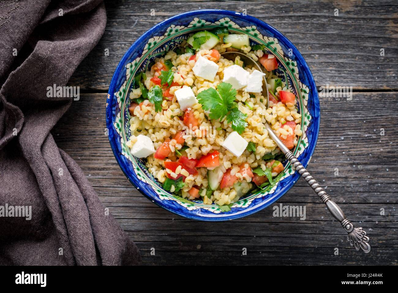 Tabbouleh salad with soft white cheese and pomegranate seeds in bowl on wooden background. Top view Stock Photo