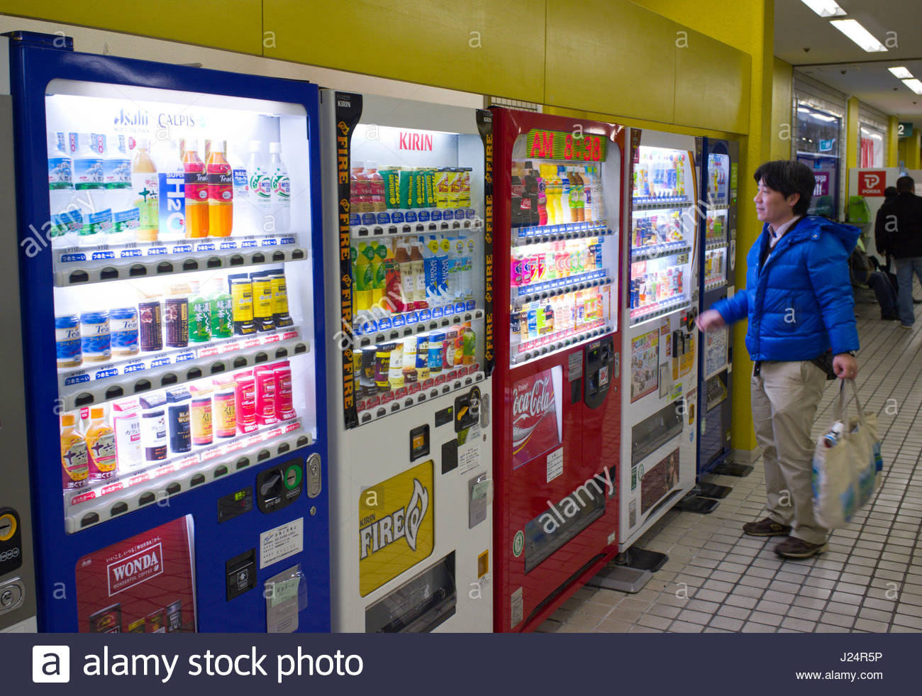Japanese man looking at drink choices offered from vending machine in bus station, Minato-ku, Tokyo, Kanto, Japan Stock Photo