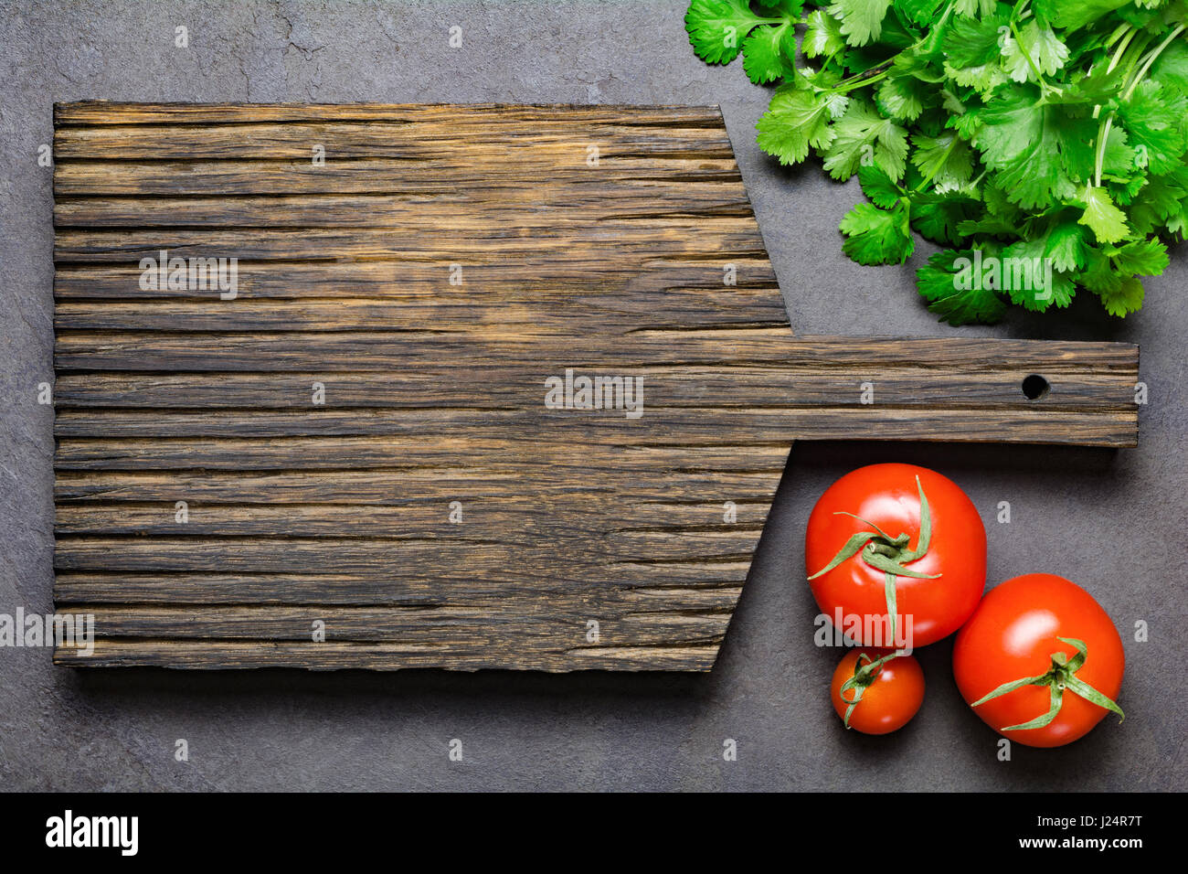 cutting board with food. Food Background: Wooden Cutting Board, Fresh Tomatoes And Bunch Of Cilantro. Copy Space For Your Text Or Design. Top View Board With