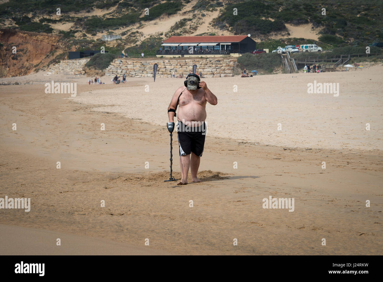 Man on a beach with a metal detector - Stock Image