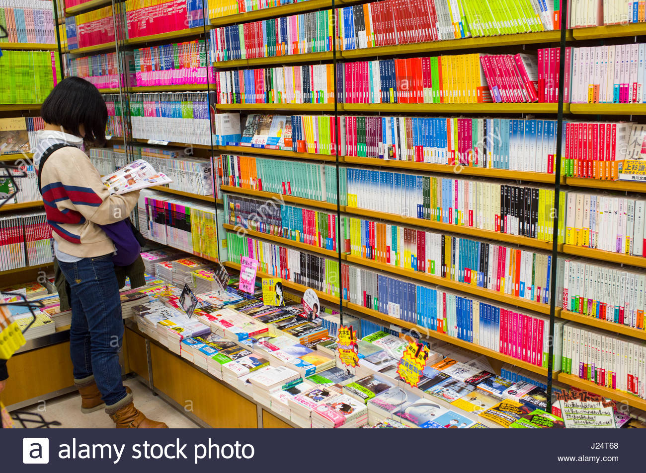 Girl reading Japanese book inside bookstore, Narita International Airport, NRT, Narita-shi, Chiba, Honshu, Japan - Stock Image