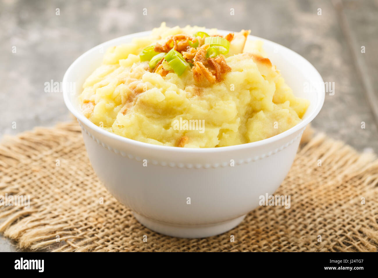 Mashed potatoes with roasted onions served in a small bowl. - Stock Image