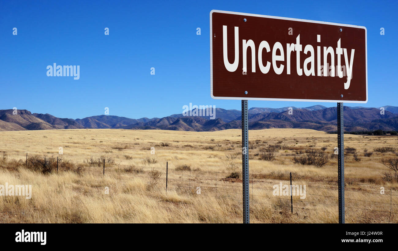 Uncertainty road sign with blue sky and wilderness Stock Photo