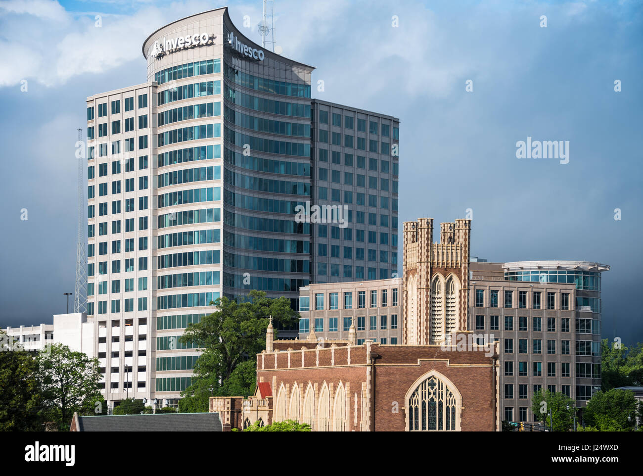 Architectural contrast along the Atlanta, Georgia skyline where the modern Invesco building towers above the Peachtree - Stock Image
