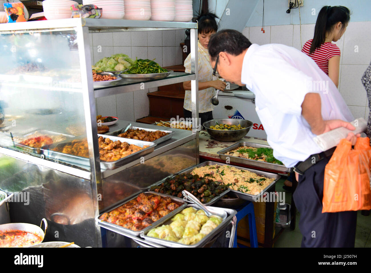 A simple Vietnamese restaurant in Hanoi. The food is on display. Many customers buy and take it as a takeaway lunch. Stock Photo