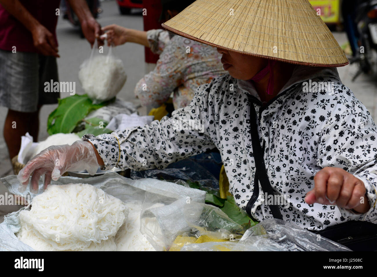 A Vietnamese woman selling fresh rice noodles. - Stock Image