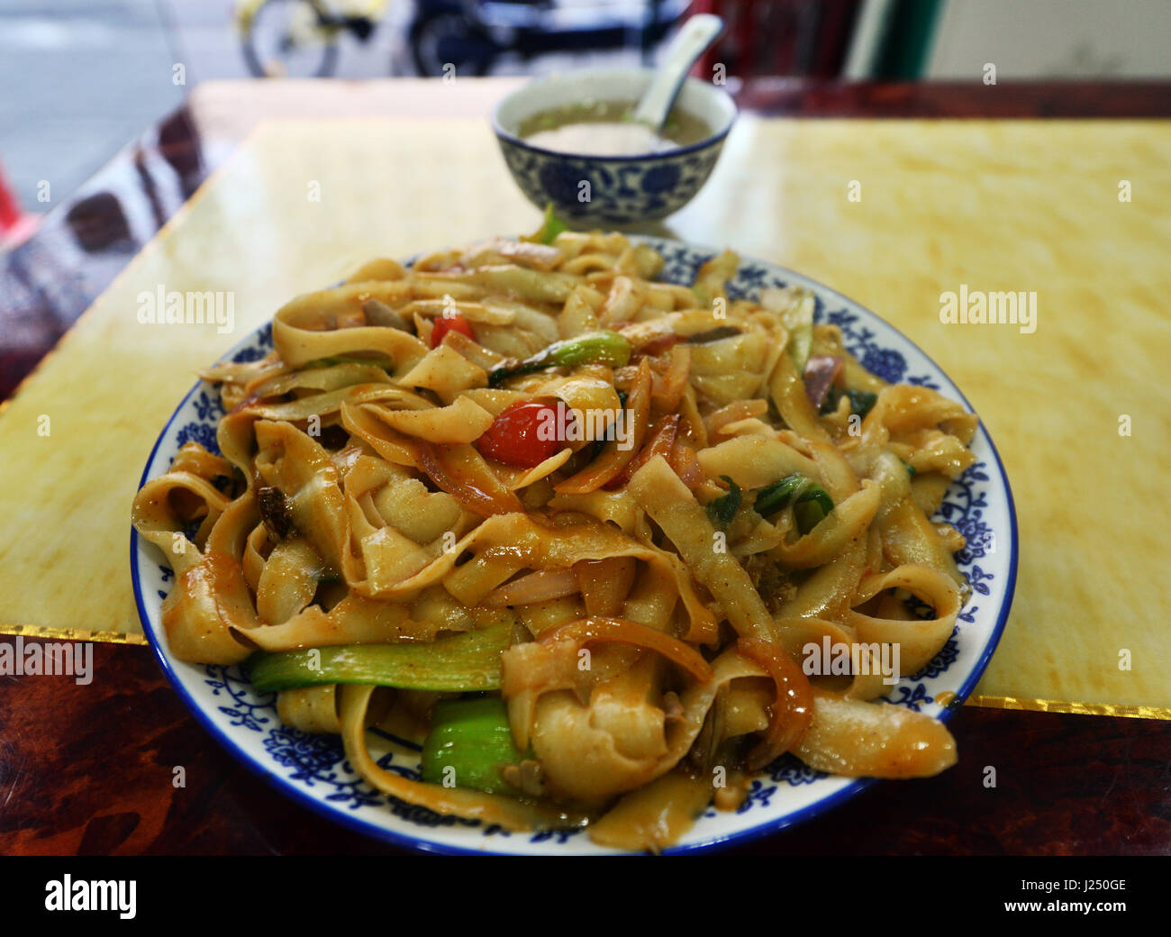 A plate of Dao Xiao Mian - Blade shaved noodles - A traditional Hui Muslim dish from Shanxi, China. - Stock Image
