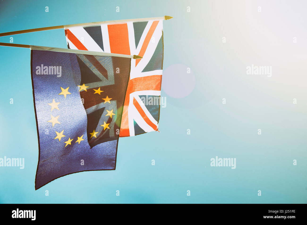 EU European Union and UK United Kingdom flags flying together in bright blue sky on the dawn of a new day of cooperation - Stock Image
