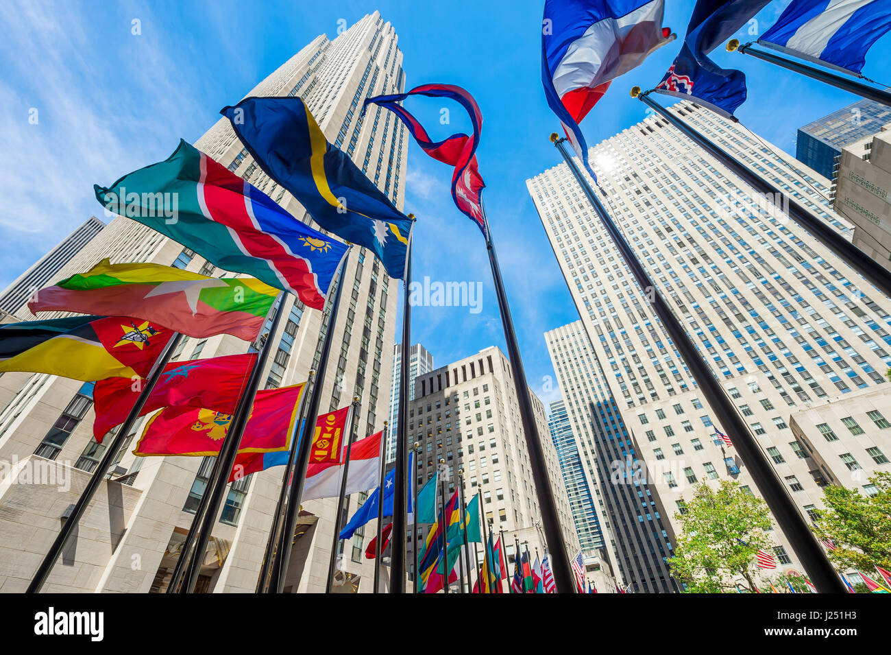 NEW YORK CITY - SEPTEMBER 2, 2016: International flags fly at the foot of the Art Deco skyscrapers at Rockefeller - Stock Image