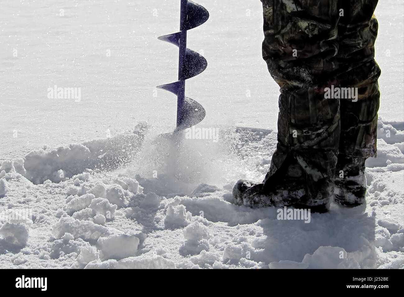 Side View of Drilling a Hole for Ice Fishing. - Stock Image
