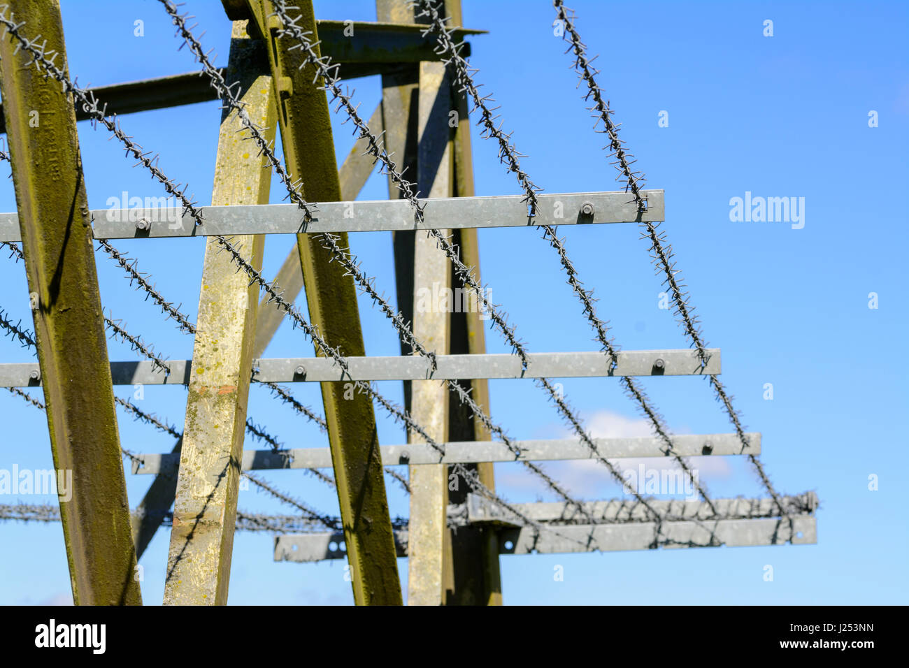 Barbed security wire on an electricity pylon. - Stock Image