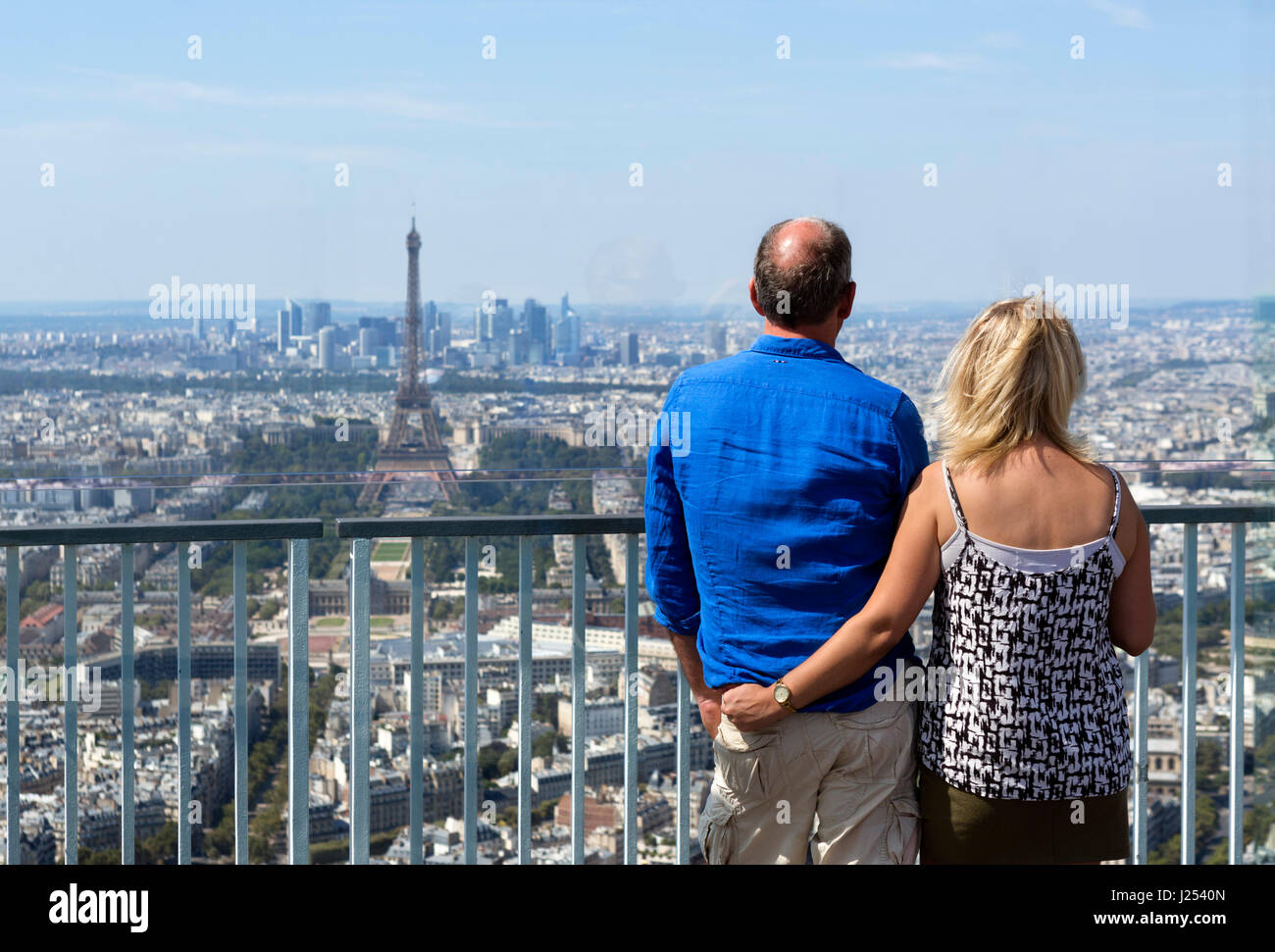 Couple on the observation deck at the top of the Tour Montparnasse, looking towards the Eiffel Tower and La Defense, Stock Photo