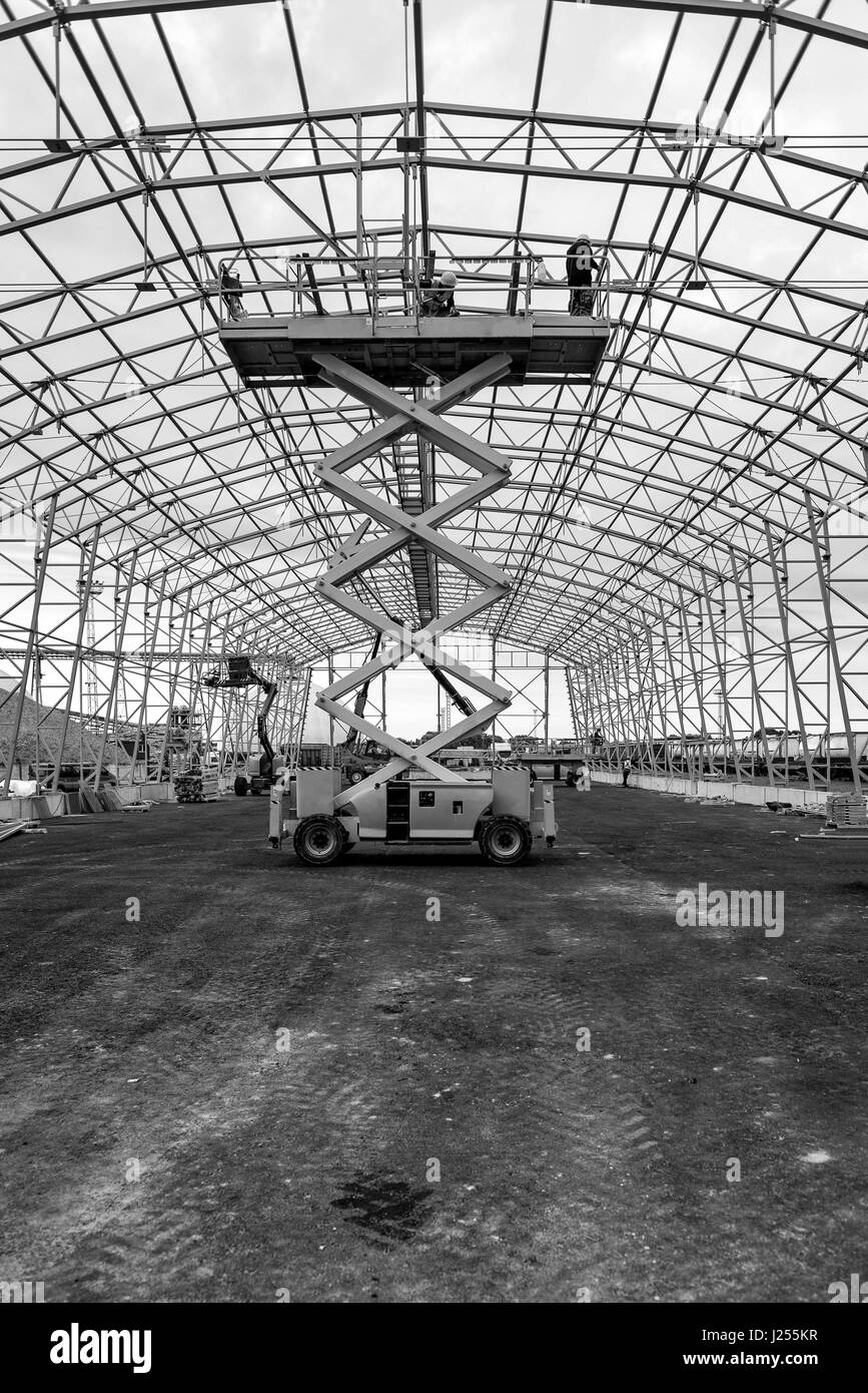 Lift with platform work in warehouse hangar construction field. - Stock Image