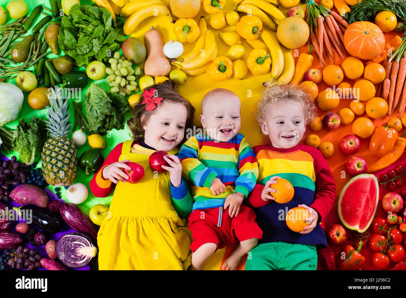 Boy, girl and baby with variety of fruit and vegetable. Colorful rainbow of raw fruits and vegetables. Child eating - Stock Image