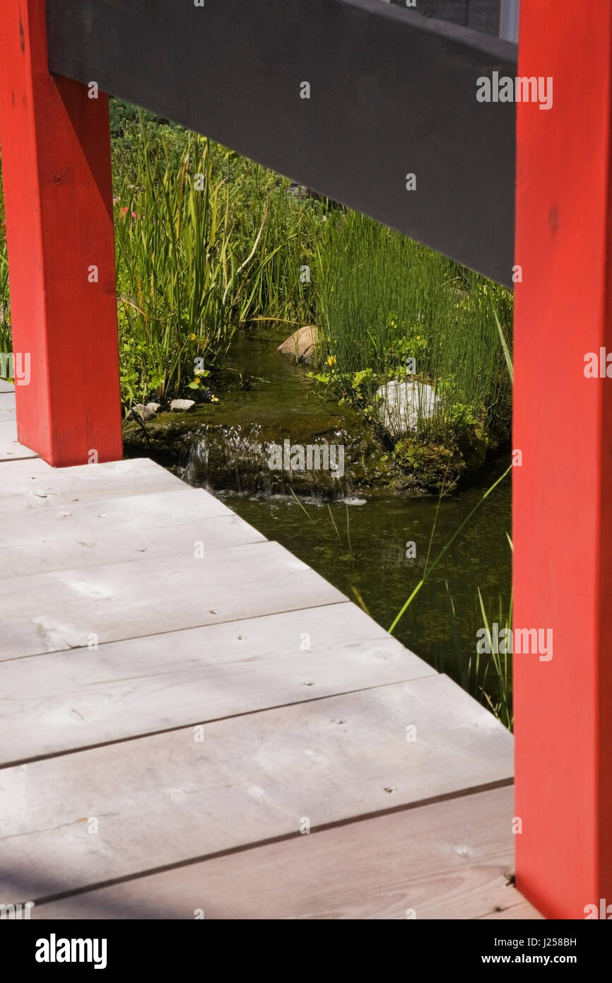 View Of A Small Waterfall In An Ornamental Pond Through A Wooden