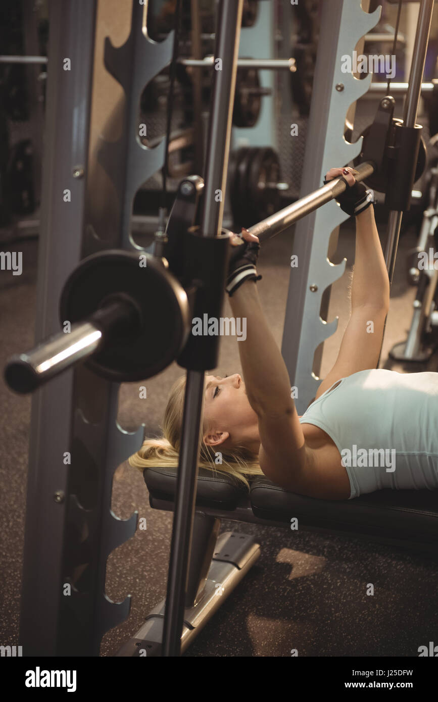 Fit woman exercising with smith machine in the gym - Stock Image