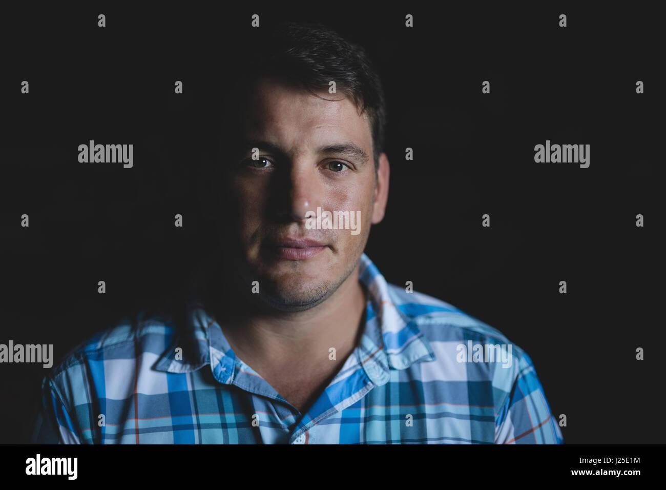Portrait of confident man against black background - Stock Image