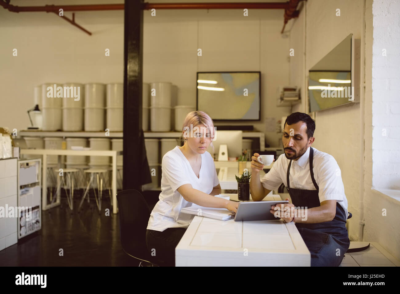 Male and female barista having coffee while using digital tablet in coffee shop - Stock Image