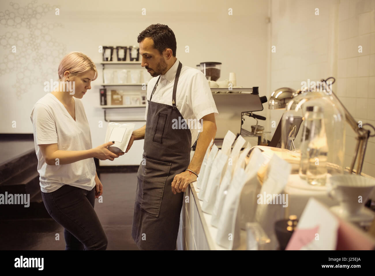 Male and female barista checking packaging of coffee in coffee shop - Stock Image