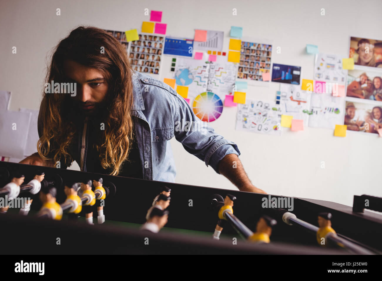 Concentrated man playing table football game - Stock Image