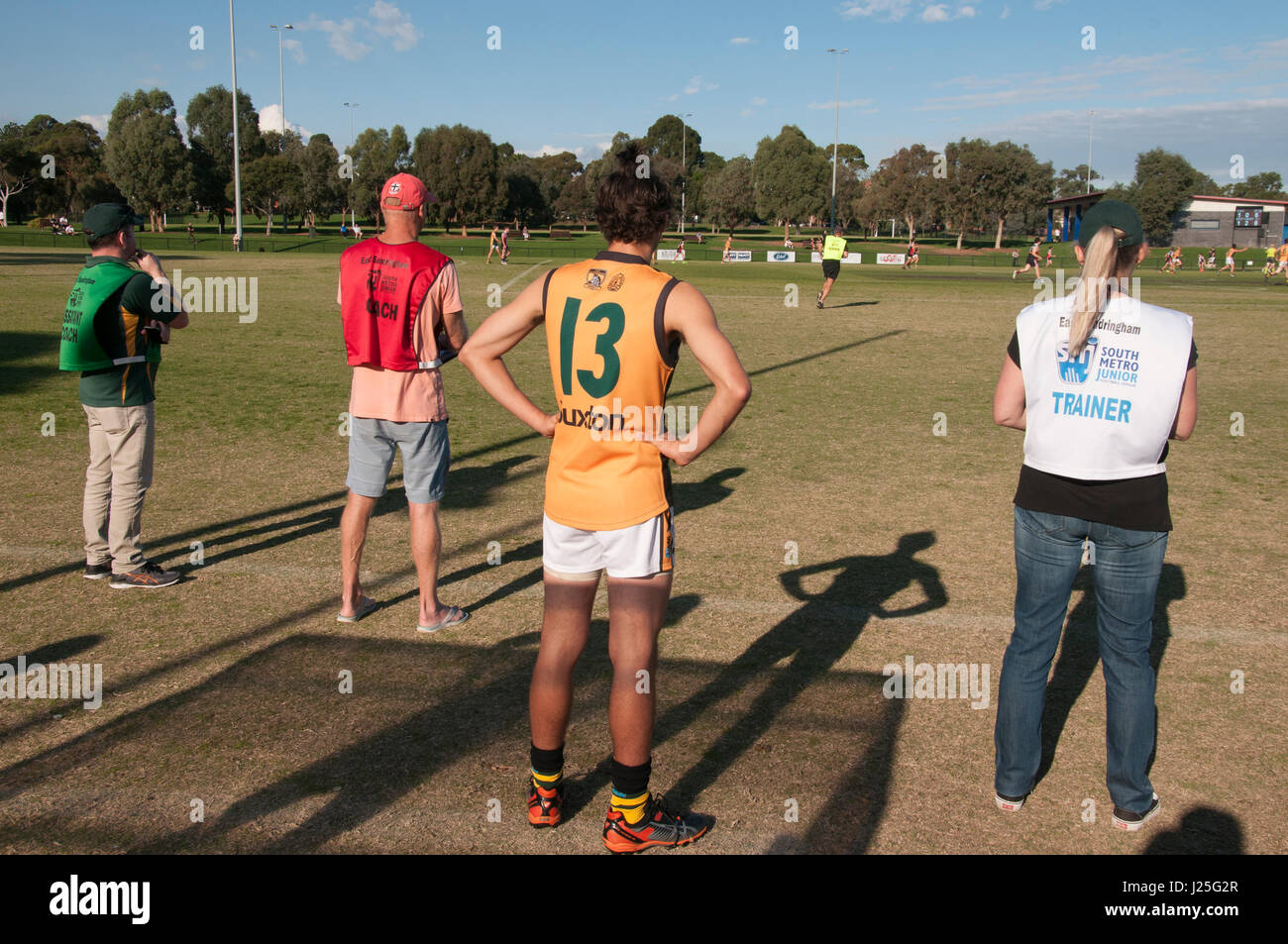 Team officials watch an Amateur Australian Rules football match in suburban Melbourne, Australia - Stock Image